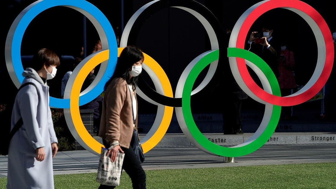Women wearing protective face masks following an outbreak of the coronavirus disease walk past the Olympic rings in Tokyo. (File photo: Reuters)