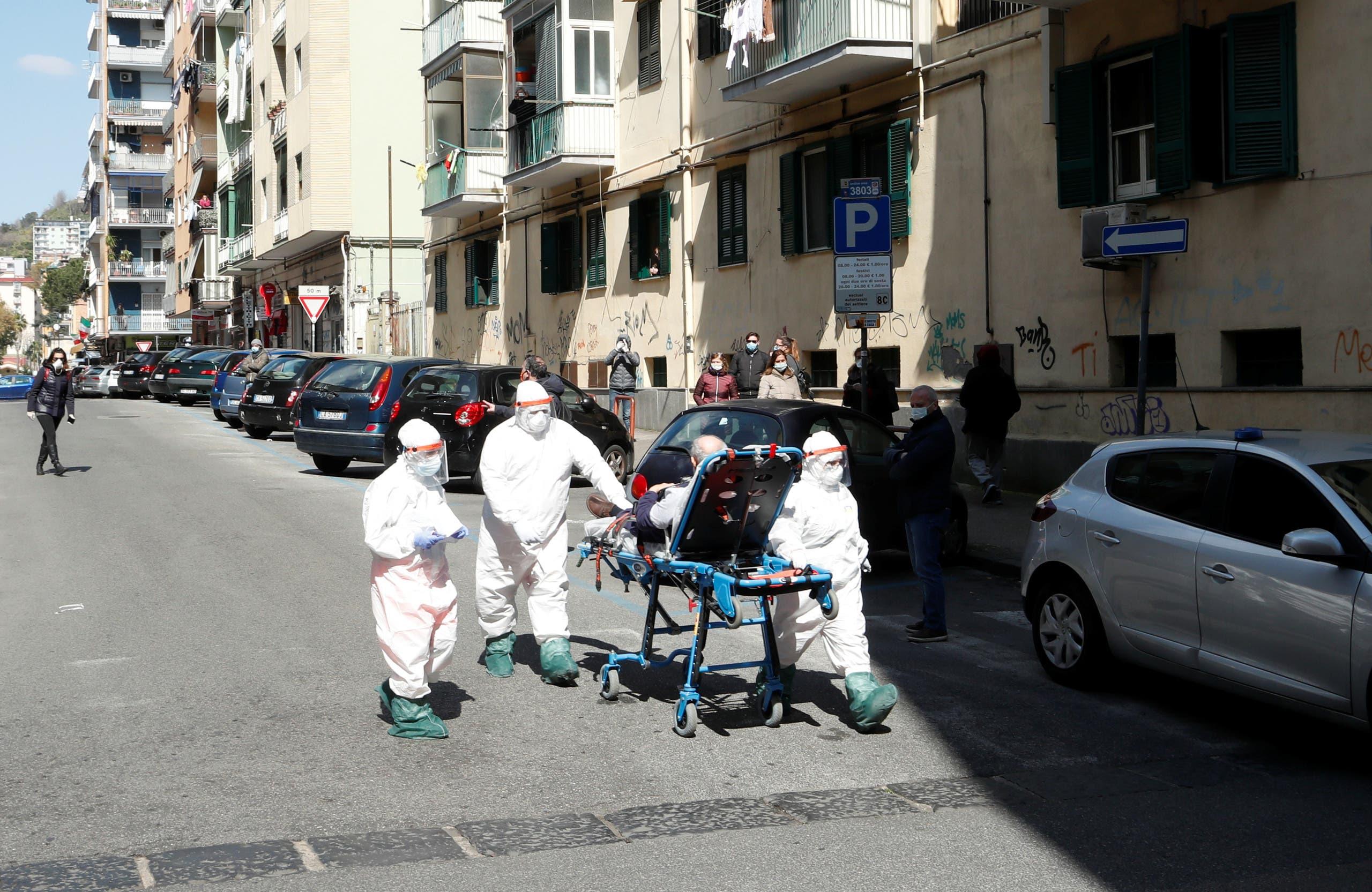 أفراد من الرعاية الصحية مع أحد المرضى في نابولي يوم 2 أبريل (من رويترز)
