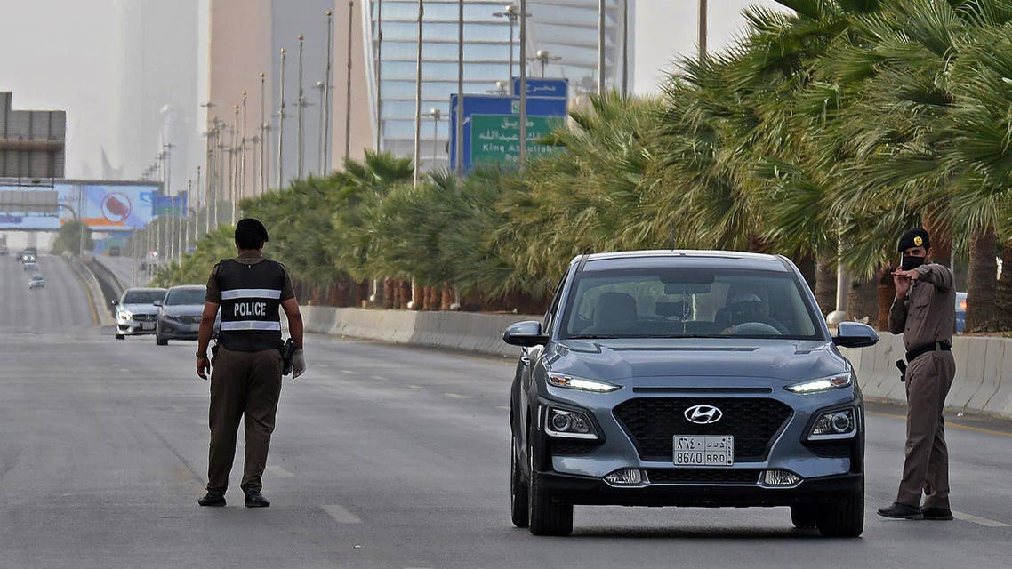 Saudi policemen manning a checkpoint on King Fahd road in the capital Riyadh, after the Kingdom began implementing an 11-hour nationwide curfew. (AFP)
