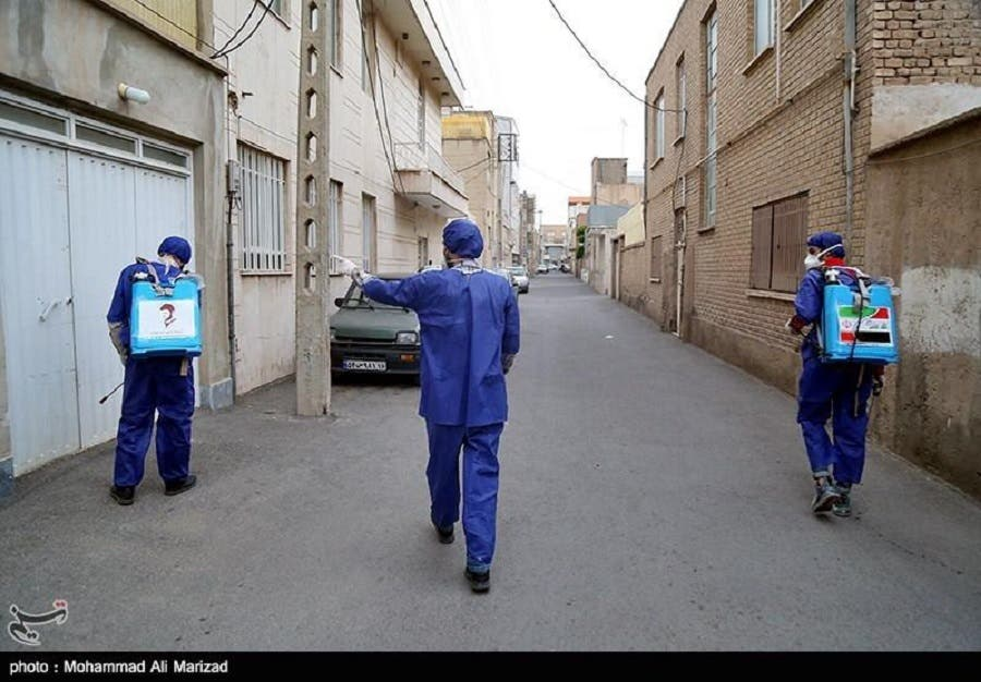 Members of the PMU sterilized walls and entrances to homes and distributed bottles of disinfectant in Qom. (Tasnim)