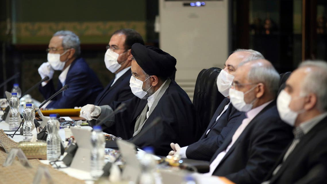 In this photo released by the official website of the Office of the Iranian Presidency, cabinet members wearing face masks and gloves attend their meeting in Tehran, Iran, Wednesday, March 18, 2020. For most people, the new coronavirus causes only mild or moderate symptoms. For some it can cause more severe illness. (Office of the Iranian Presidency via AP)
