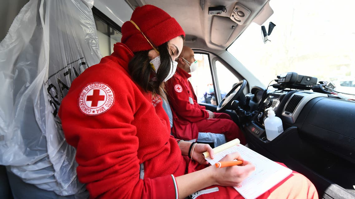 Members of the Red Cross sit inside a vehicle outside the Molinette Hospital on Palm Sunday, during the coronavirus disease (COVID-19) outbreak, in Turin, Italy April 5, 2020. REUTERS/Massimo Pinca