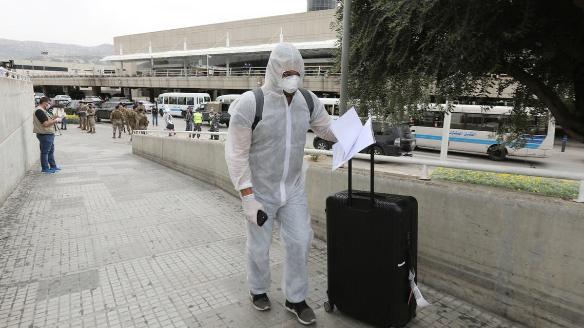 Lebanese people, who were stranded abroad by coronavirus lockdowns, are pictured wearing face masks and gloves as they hold their luggage upon arrival at Beirut's international airport, Lebanon April 5, 2020. REUTERS/Mohamed Azakir