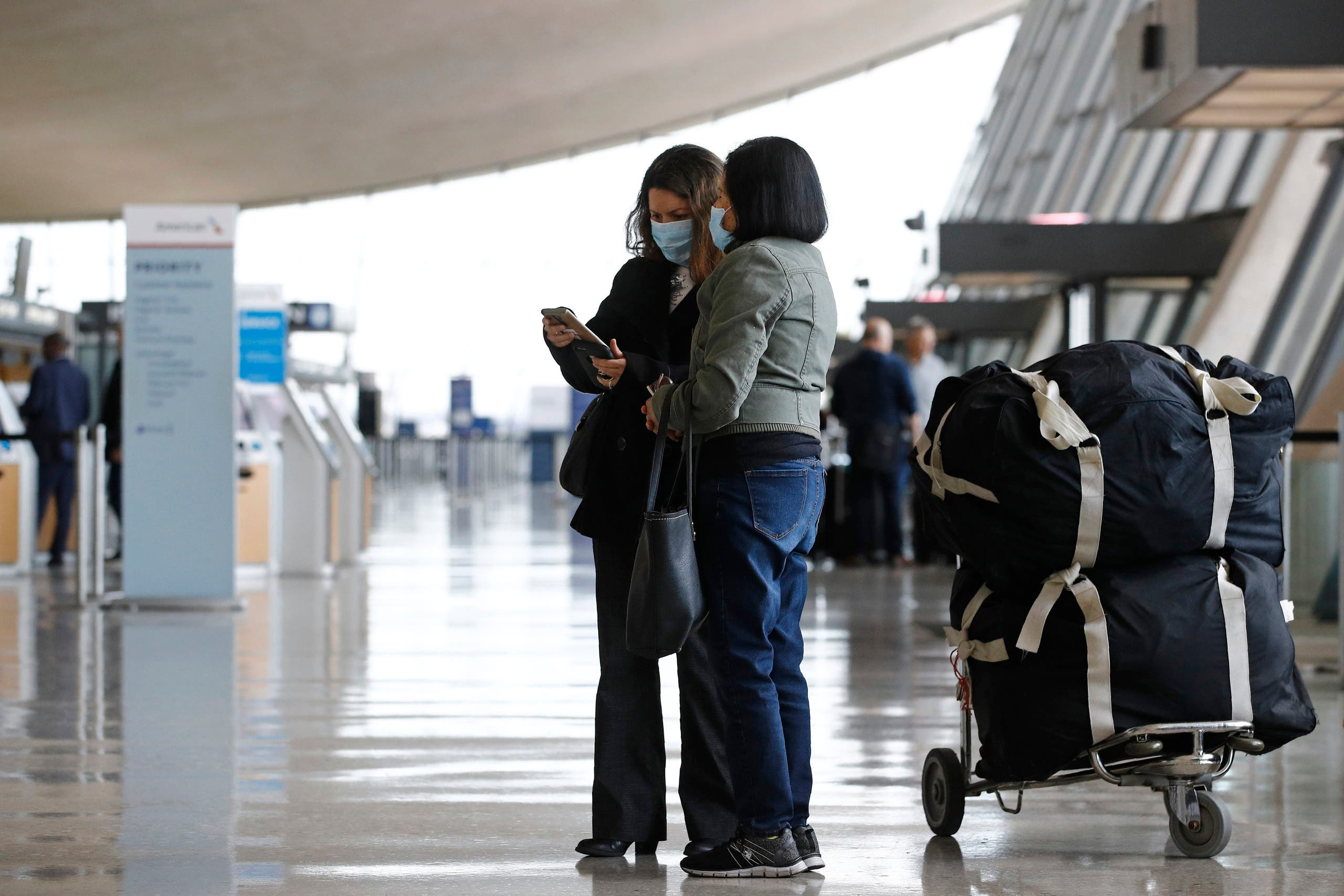 Travelers wear face masks as they prepare to check in for a flight at Dulles International Airport in Dulles, Va., Tuesday, March 17, 2020. (AP)