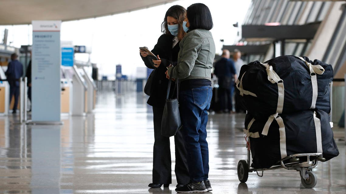 Travelers wear face masks as they prepare to check in for a flight at Dulles International Airport, March 17, 2020. (AP)