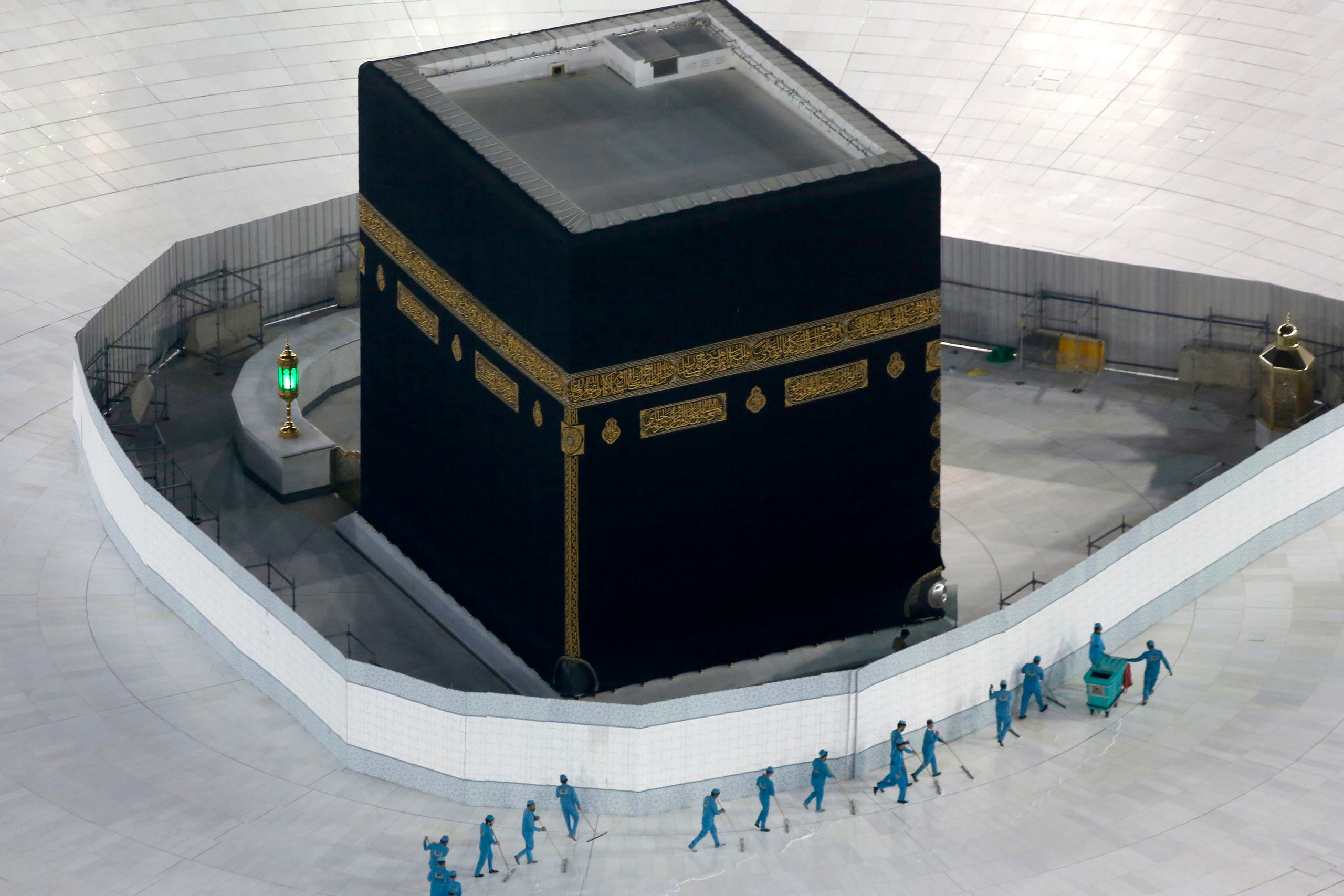 Workers disinfect the ground around the Kaaba, the cubic building at the Grand Mosque, in the Muslim holy city of Mecca, Saudi Arabia, Saturday, March 7, 2020. (AP)