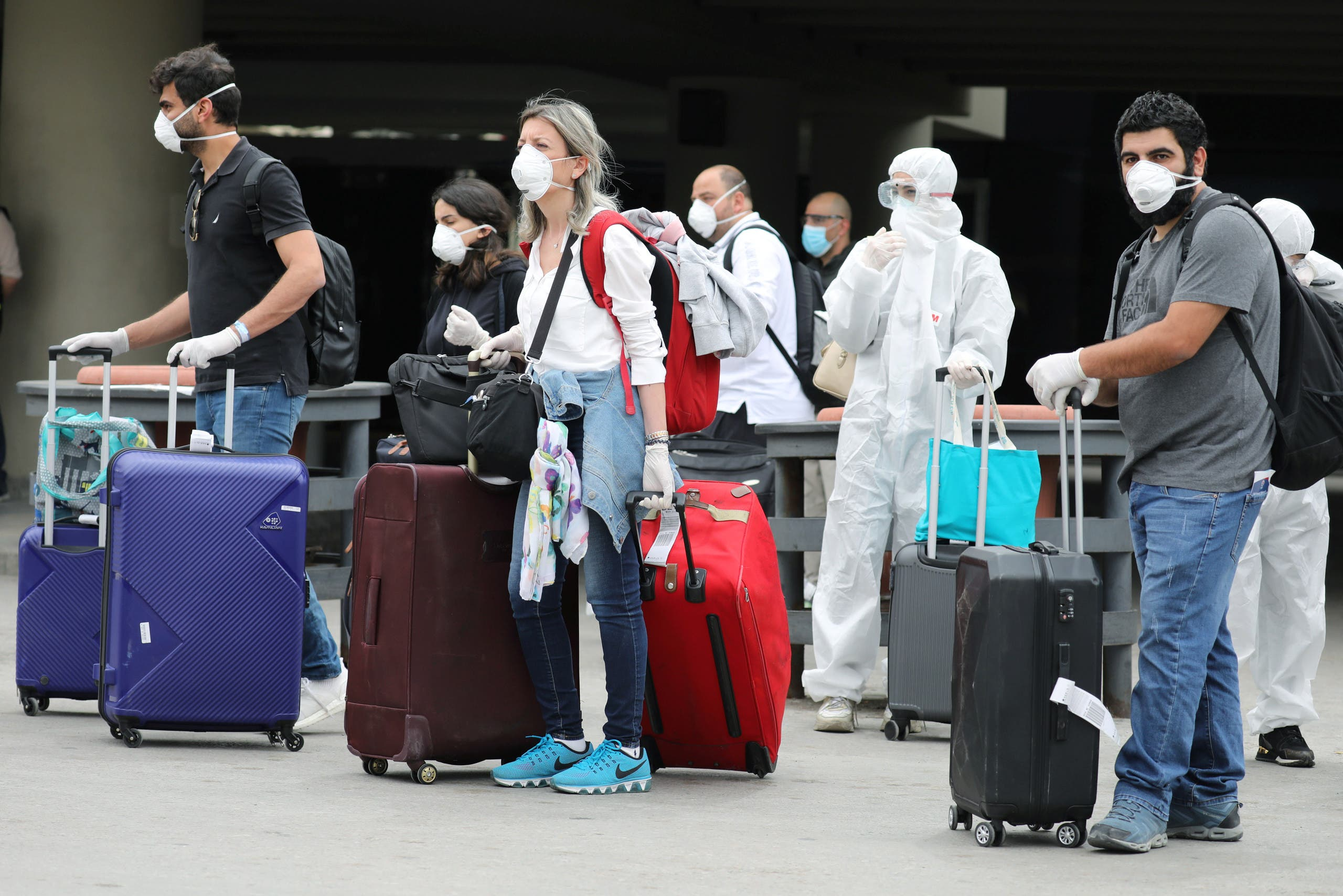 Lebanese people, who were stranded abroad by coronavirus lockdowns, are pictured wearing face masks and gloves as they hold their luggage upon arrival at Beirut's international airport, Lebanon April 5, 2020. (Reuters)