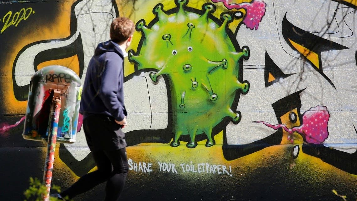 A man passes a graffiti on a wall during the coronavirus disease (COVID-19) outbreak in Vienna, Austria. (Reuters)