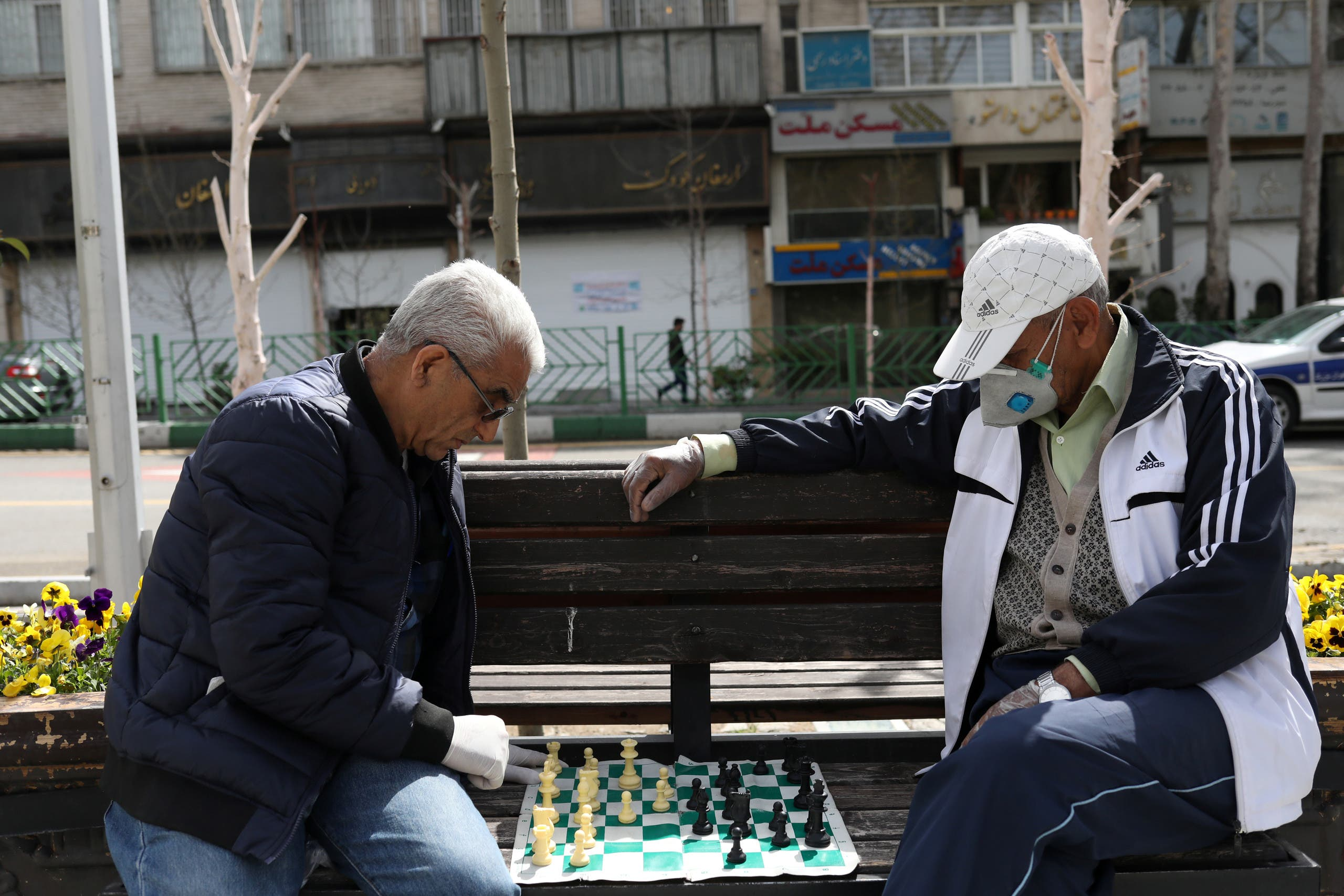 Men wear protective face masks and gloves, amid fear of coronavirus, play chess on the sidewalk of Mellat Park, in Tehran, Iran April 2, 2020. (WANA (West Asia News Agency)/Ali Khara via Reuters)