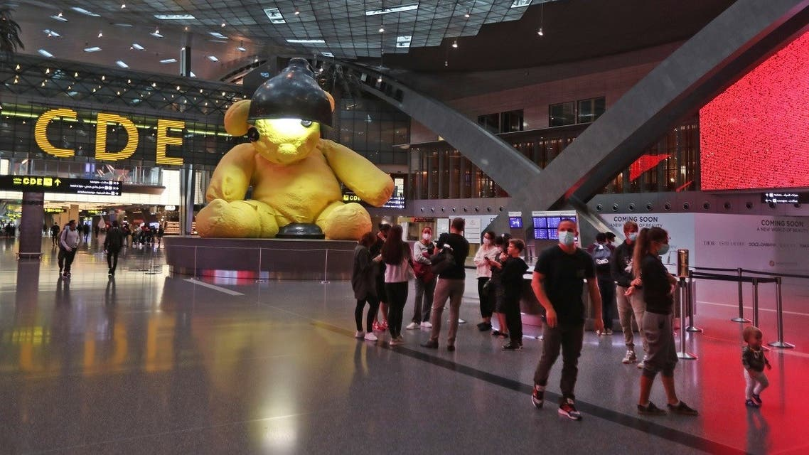 Travellers wearing masks walk past a giant 23-foot-long canary-yellow sculpture of a teddy bear sitting inside a lamp, at Hamad International Airport in the Qatari capital Doha. (File photo: AFP)