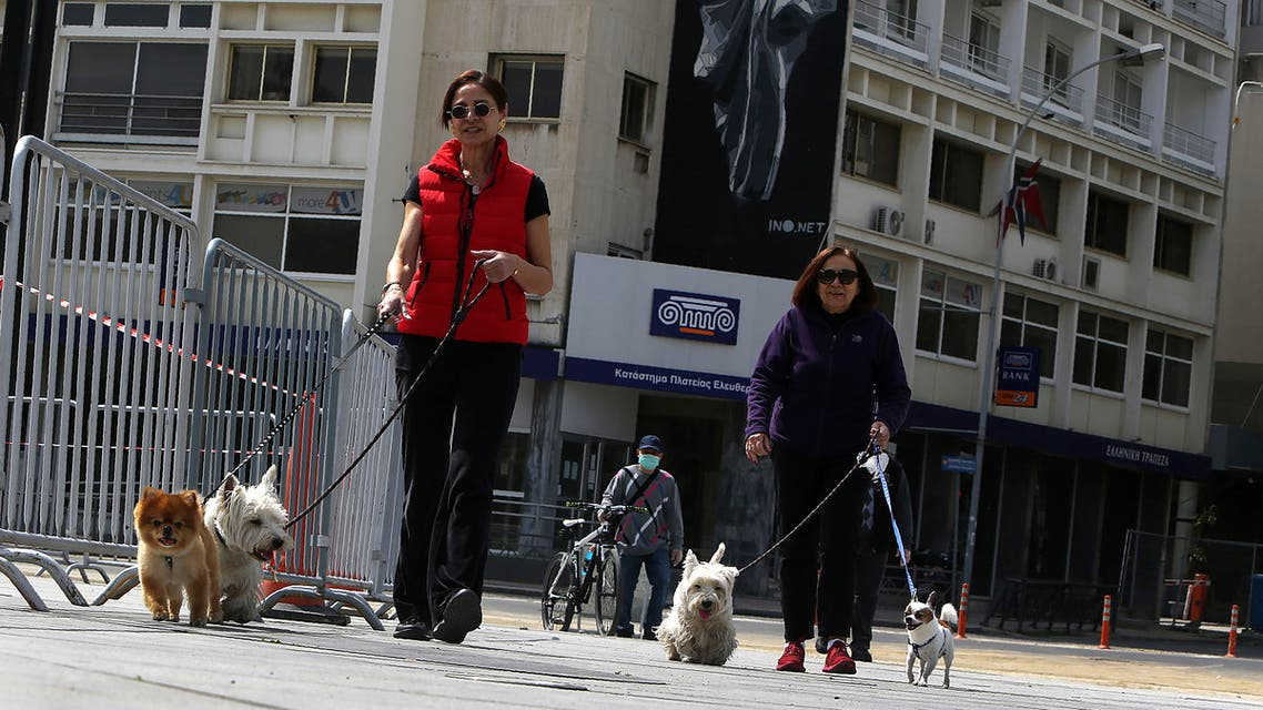 Women with their dogs walk at the deserted Elepftherias, Liberty, square in central Nicosia, Cyprus, Wednesday, March 25, 2020. Cyprus has issues a nationwide three-week ban on unnecessary trips outside the home to combat the spread of the coronavirus COVID-19 pandemic. For most people, the new coronavirus causes mild or moderate symptoms, such as fever and cough that clear up in two to three weeks. For some, especially older adults and people with existing health problems, it can cause more severe illness, including pneumonia and death. (AP Photo/Petros Karadjias)
