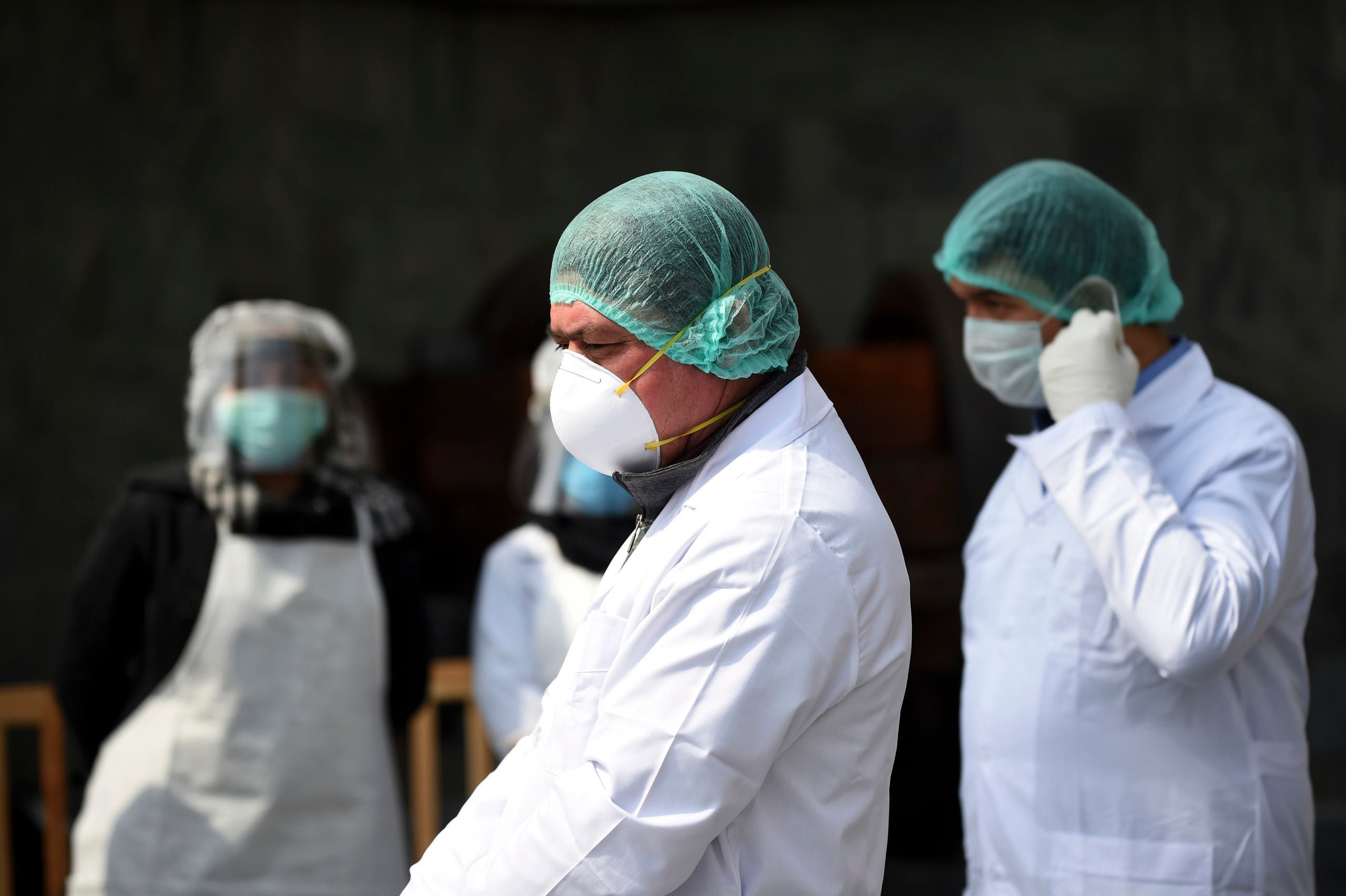 Afghan health services staff wearing protective gear, as a preventive measure against the spread of the COVID-19 coronavirus, wait to check the body temperature of guests ahead of the start of Afghanistan President Ashraf Ghani's swearing-in inauguration ceremony, at the Presidential Palace in Kabul on March 9, 2020.