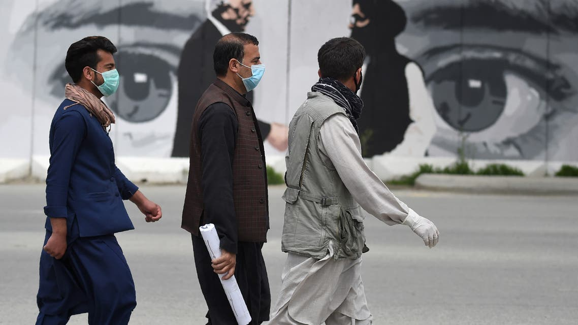 Men wearing facemasks as a precautionary measure against the COVID-19 novel coronavirus walk past a wall painted with images of US Special Representative for Afghanistan Reconciliation Zalmay Khalilzad (L) and Taliban co-founder Mullah Abdul Ghani Baradar (R), in Kabul April 5, 2020.