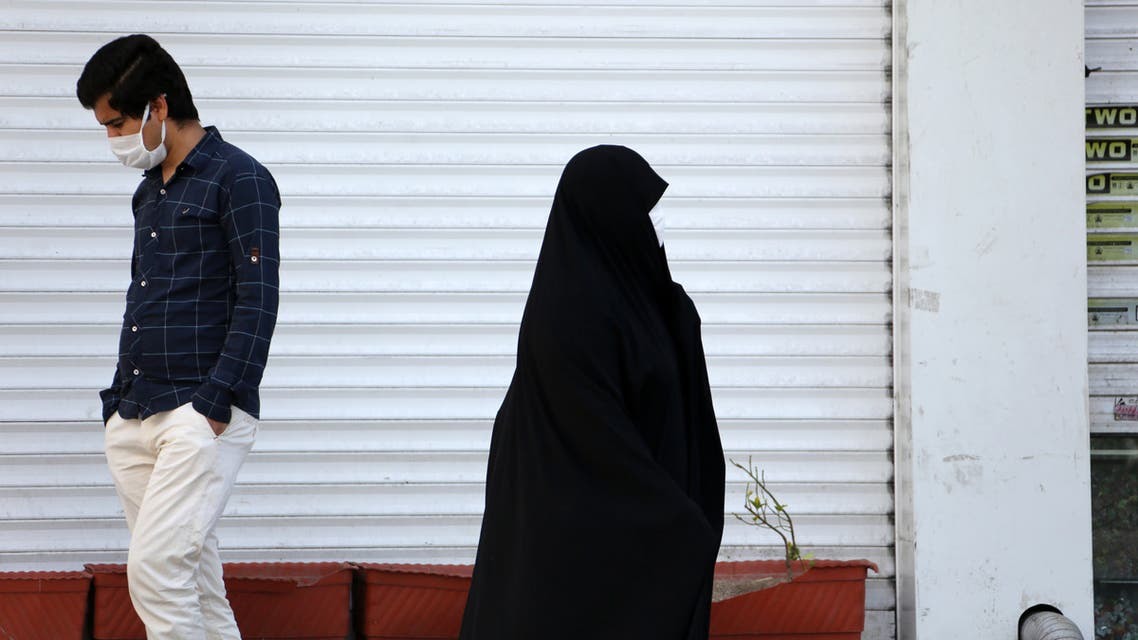 An Iranian man and a woman wearing a protective face masks against the novel coronavirus, walk past a closed shop in the capital Tehran on April 5, 2020. The spread of the virus in Iran has slowed for the fifth day in a row, according to official figures released today by the authorities, who also announced plans for a gradual resumption of certain economic activities starting on April 11.