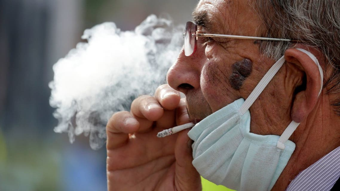 A man wearing a face mask smokes a cigaret, as Albanian authorities take measures to stop the spread of the coronavirus disease (COVID-19) in Tirana, Albania April 6, 2020. REUTERS/Florion Goga