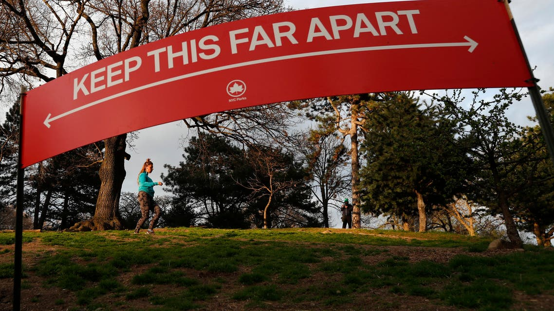 A woman jogs in Brooklyn's Fort Greeene park, Sunday, April 5, 2020, beneath a sign demonstrating the distance people should keep from each other during the coronavirus outbreak in New York. People have been urged to cover their faces and stay at least six feet apart during to avoid contracting COVID-19. (AP