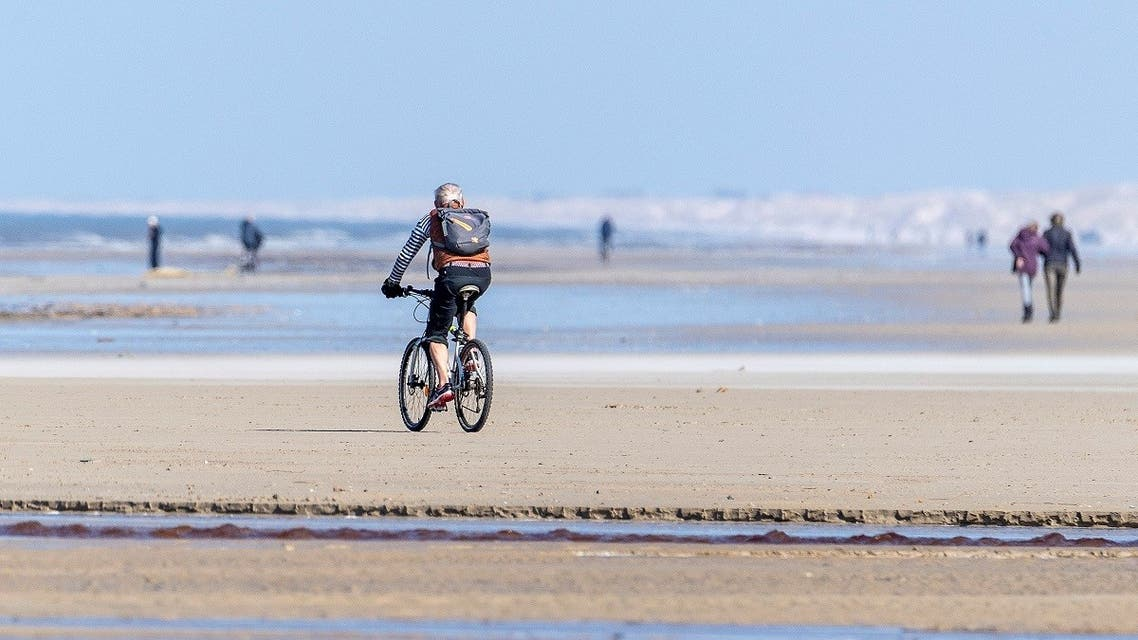 A cyclist rides on a beach amid the coronavirus disease (COVID-19) spread, at Vejers Strand, Jutland, Denmark. (File photo: Reuters)