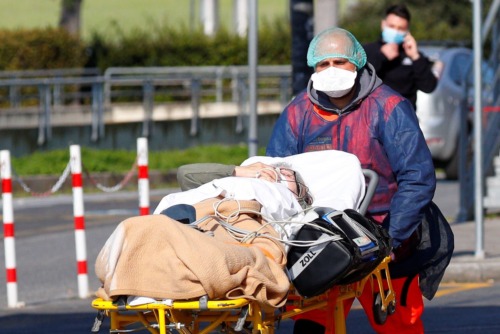 أحد العاملين بالرعاية الصحية ينقل مريضا في روما (أرشيفية- رويترز)