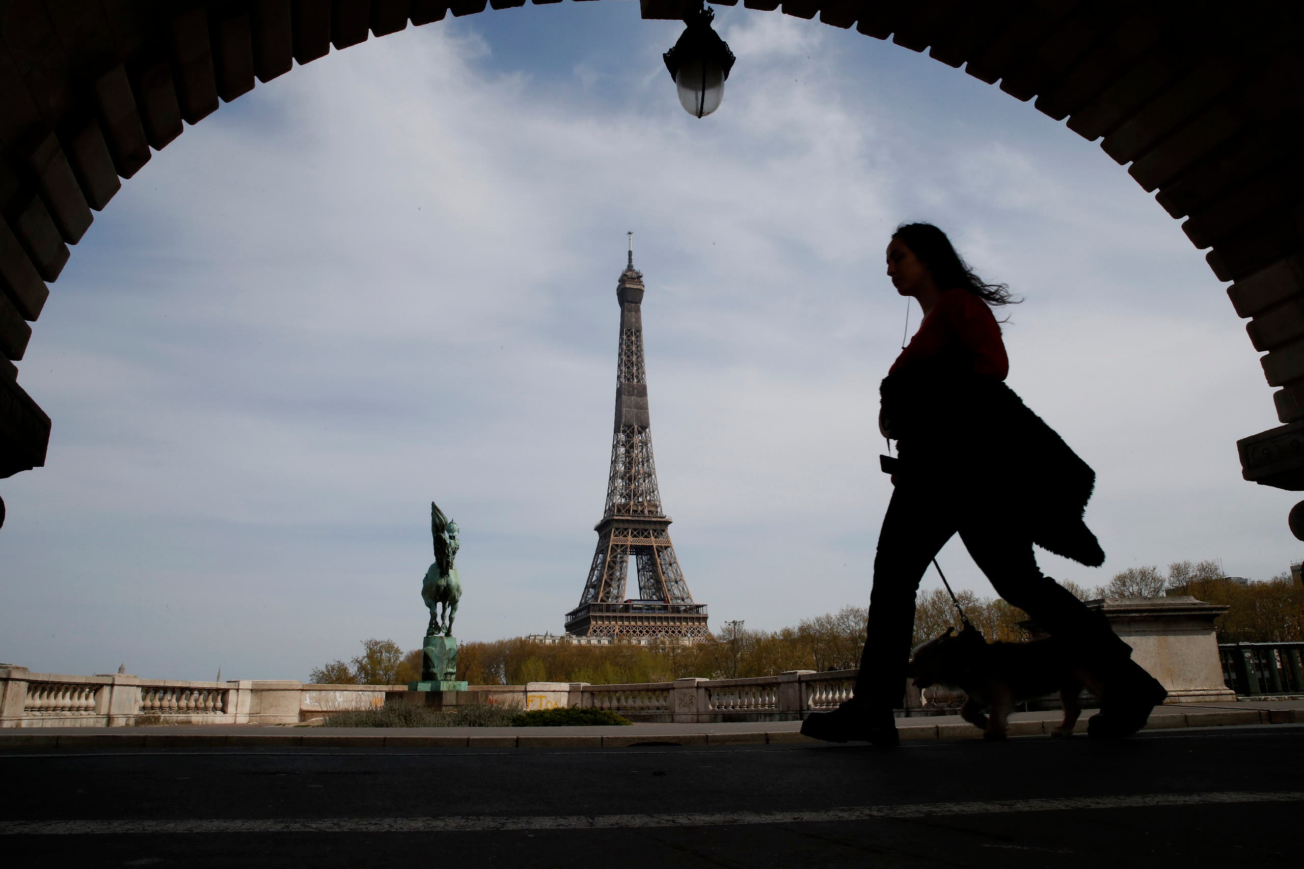 A woman walks her dog on a Paris bridge, with the Eiffel tower seen in background, during a nationwide confinement to counter the COVID-19, Tuesday, April 7, 2020. (AP)
