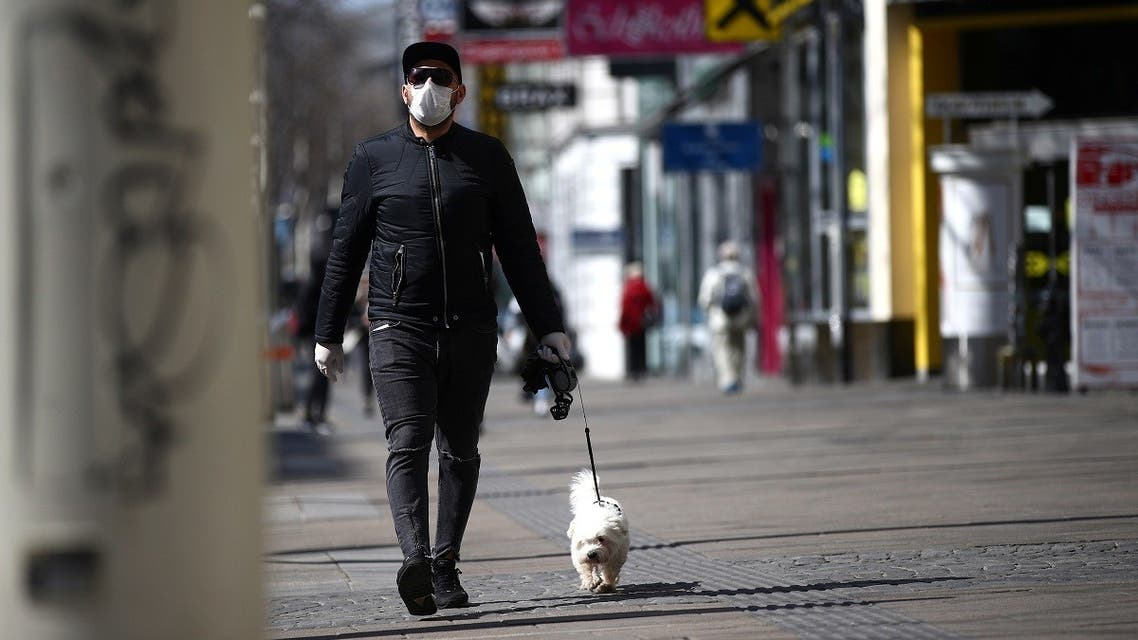 A man wearing a protective mask walks a dog on a shopping street during the global coronavirus disease (COVID-19) outbreak in Vienna. (Reuters)