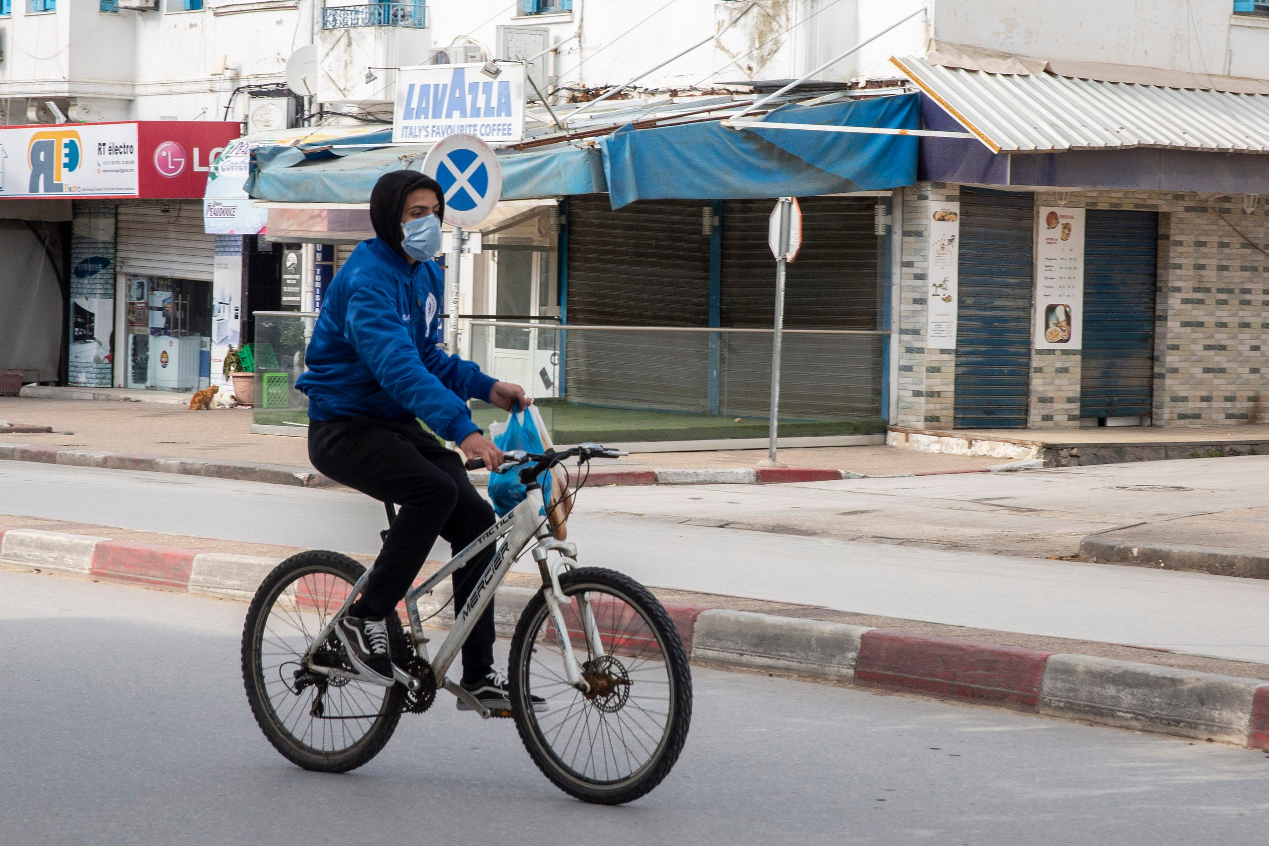 A man wearing a mask rides his bicycle after shopping in a deserted street of La Marsa, outside Tunis on March 26, 2020. (AP)