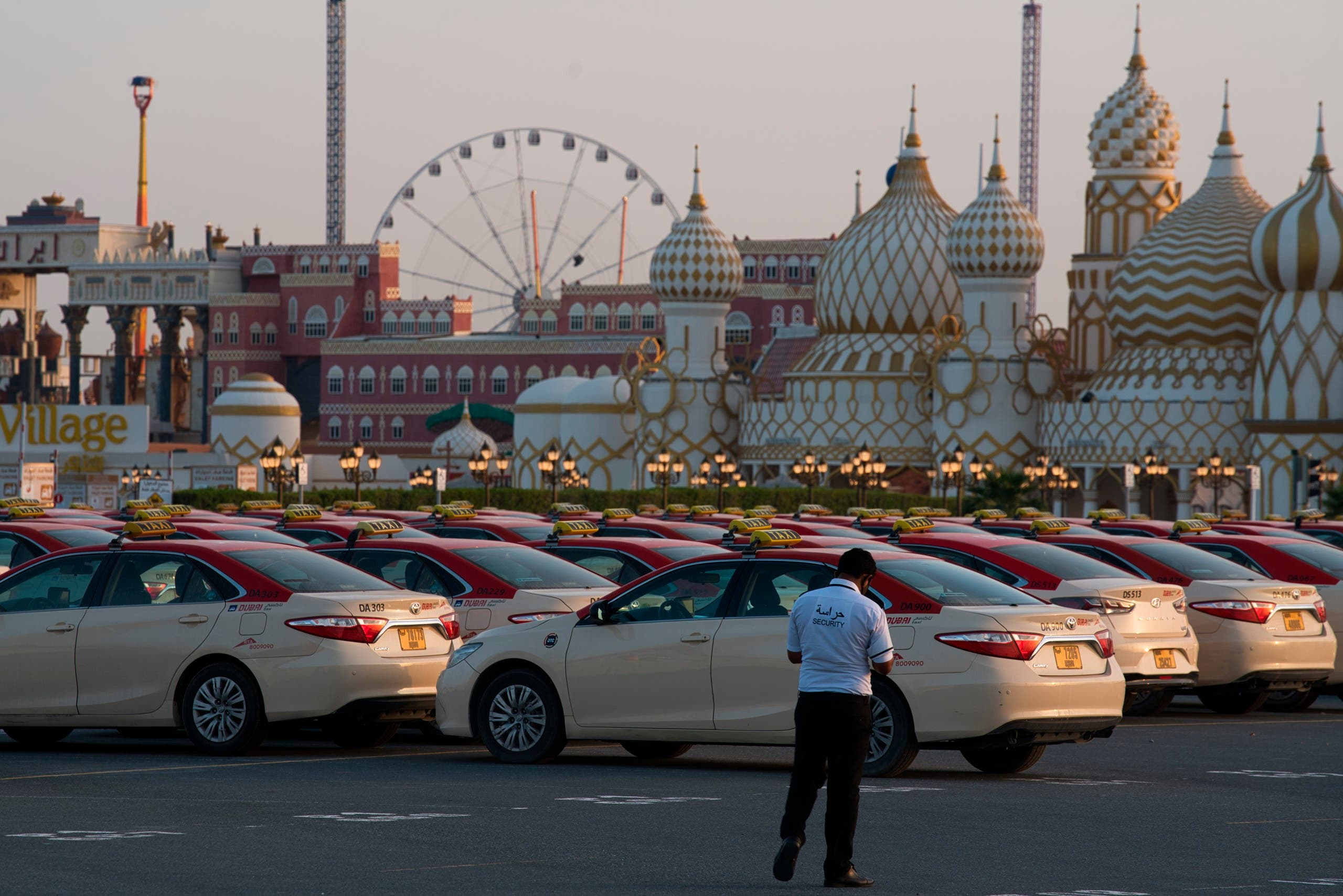 A security guard keeps watch over hundreds of taxi cabs parked at the shopping theme park Global Village in Dubai, United Arab Emirates,  on Tuesday, April 7, 2020.  (AP)