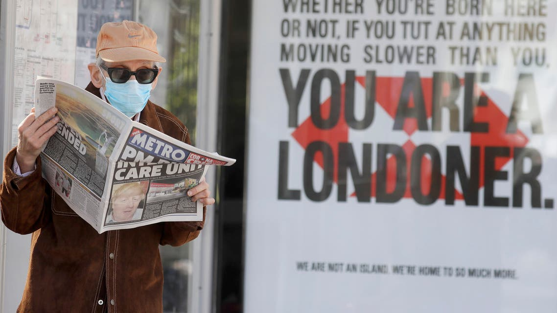 A man in the UK reads the newspaper a headline about Boris Johnson being in hospital against the backdrop of a sign which says You are a Londoner. (AP)