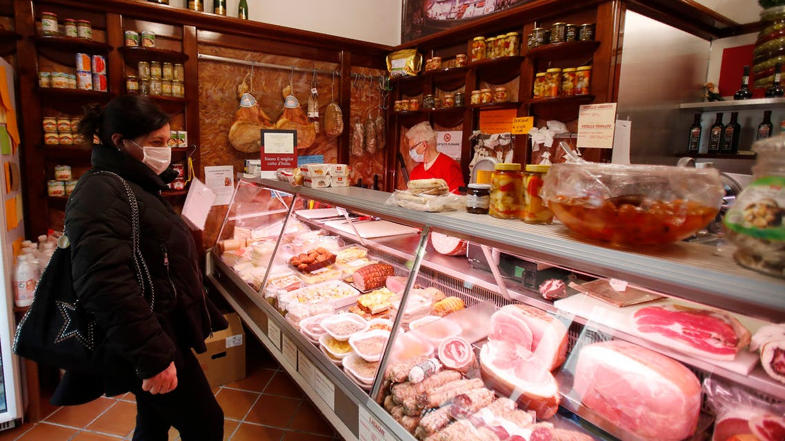 A customer wearing a mask stands in a deli meat and cold cuts shop in Codogno, Italy on March 12, 2020. (AP)