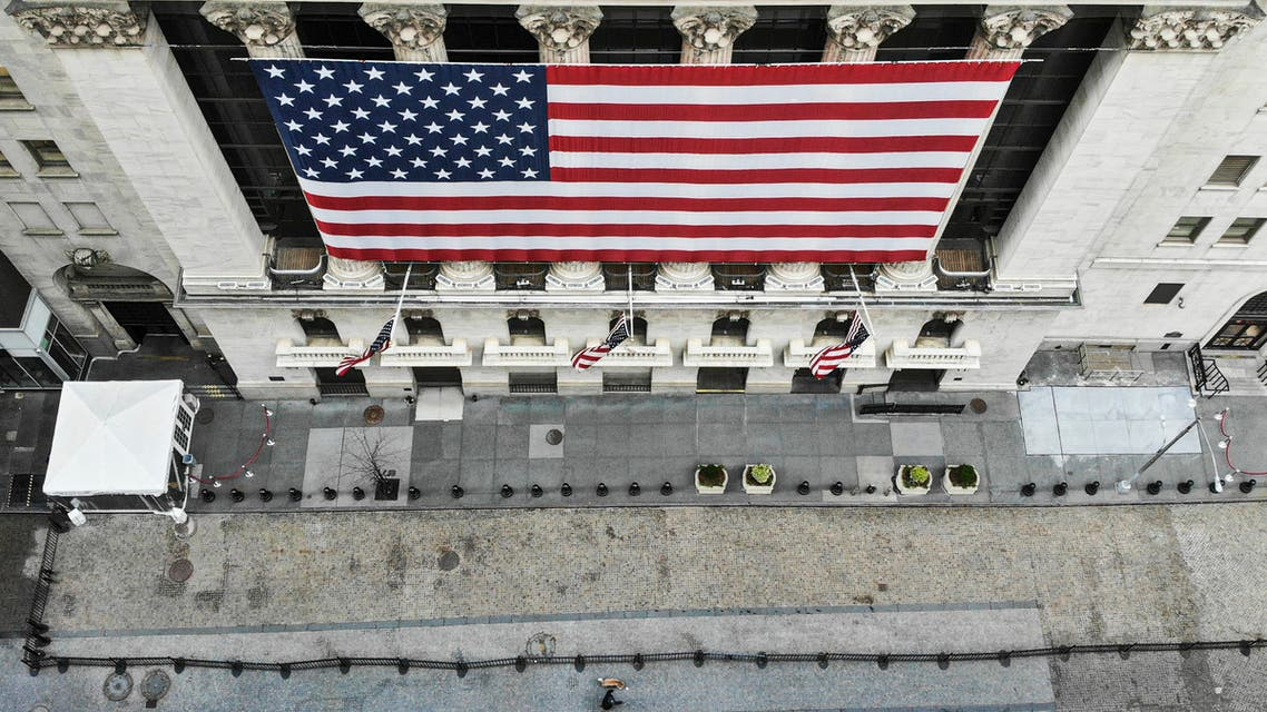 a lone pedestrian walks his dog past the New York Stock Exchange as COVID-19 concerns empty a typically bustling downtown area in New York.
