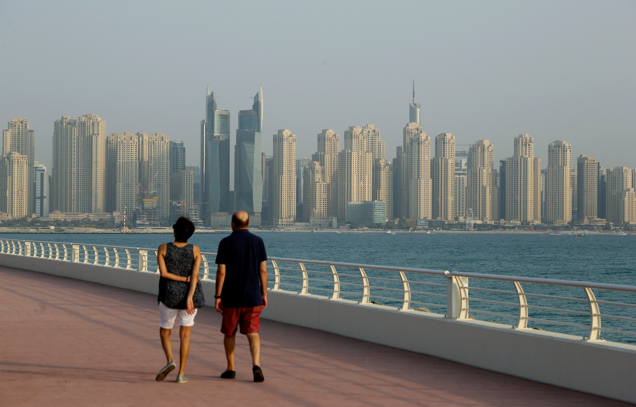 A couple walks at Palm Jumeirah island against the backdrop of Marina Waterfront skyline in Dubai, United Arab Emirates, Saturday, Sept. 22, 2018. (AP Photo)