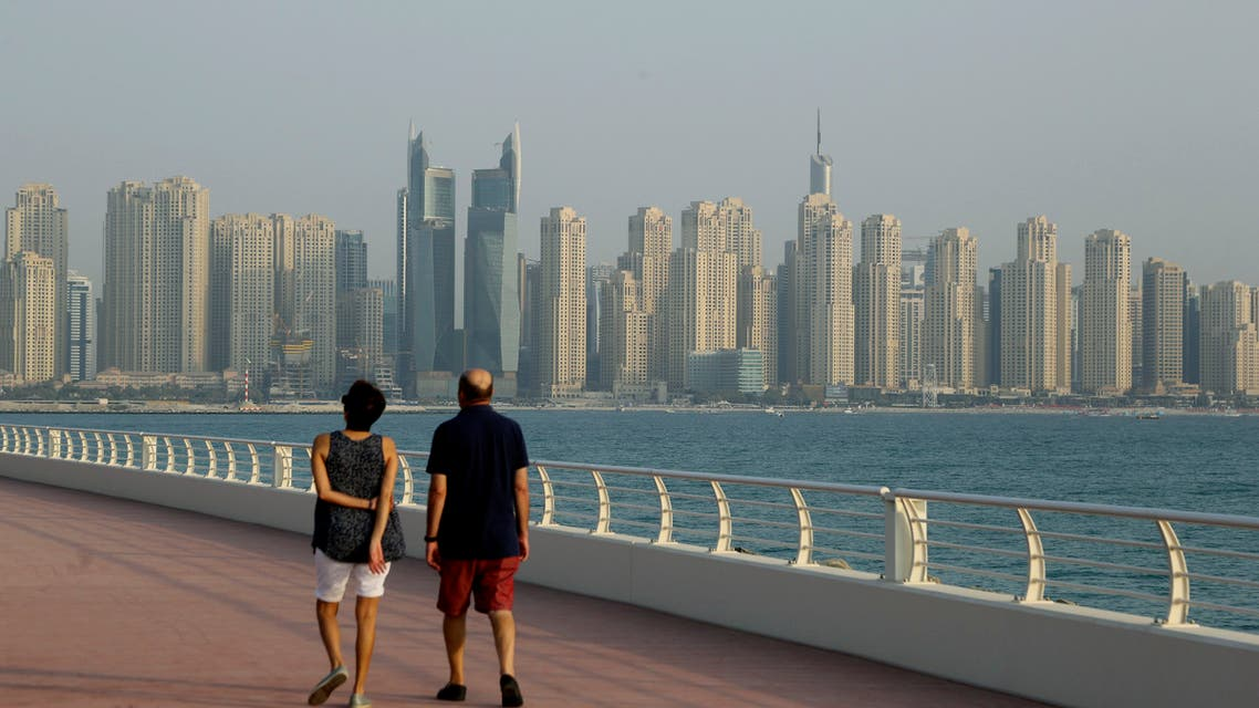 A couple walks at Palm Jumeirah island against the backdrop of Marina Waterfront skyline in Dubai, United Arab Emirates, Saturday, Sept. 22, 2018. (AP Photo)