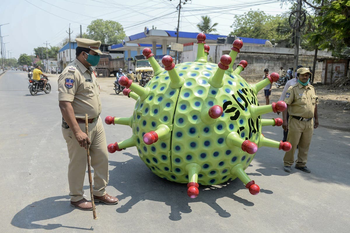 Police officers patrol as inventor Sudhakar Yadav (inside) leads his coronavirus-themed made car on a road for an awareness campaign in Hyderabad on April 8, 2020. (AFP)