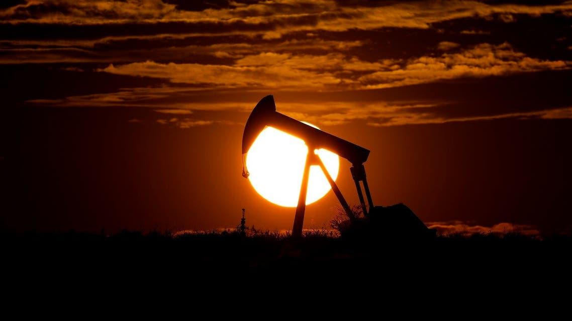 The sun sets behind an idle pump jack near Karnes City, Texas. (AP)