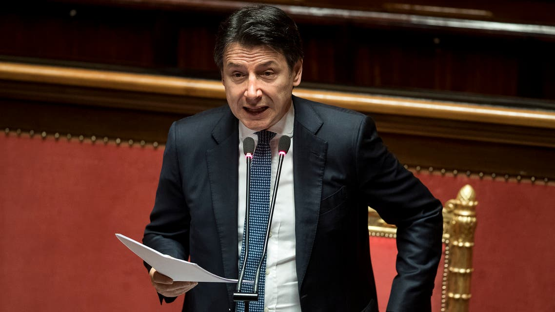 Italian Premier Giuseppe Conte adjusts his jacket as he refers to parliament on the ongoing Covid-19 situation, in Rome on March 26, 2020. (AP)