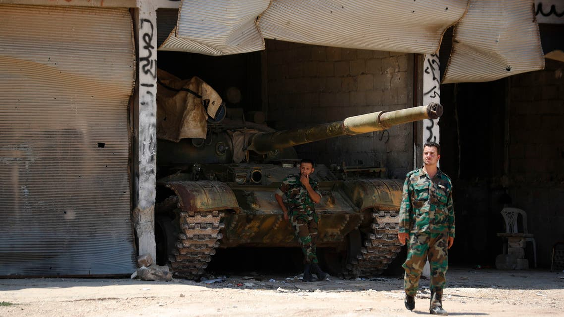 Syrian soldiers stand guard at their military post on the entrance of the central Syrian town of Rastan, Homs province, Syria on July 17, 2018. (AP)