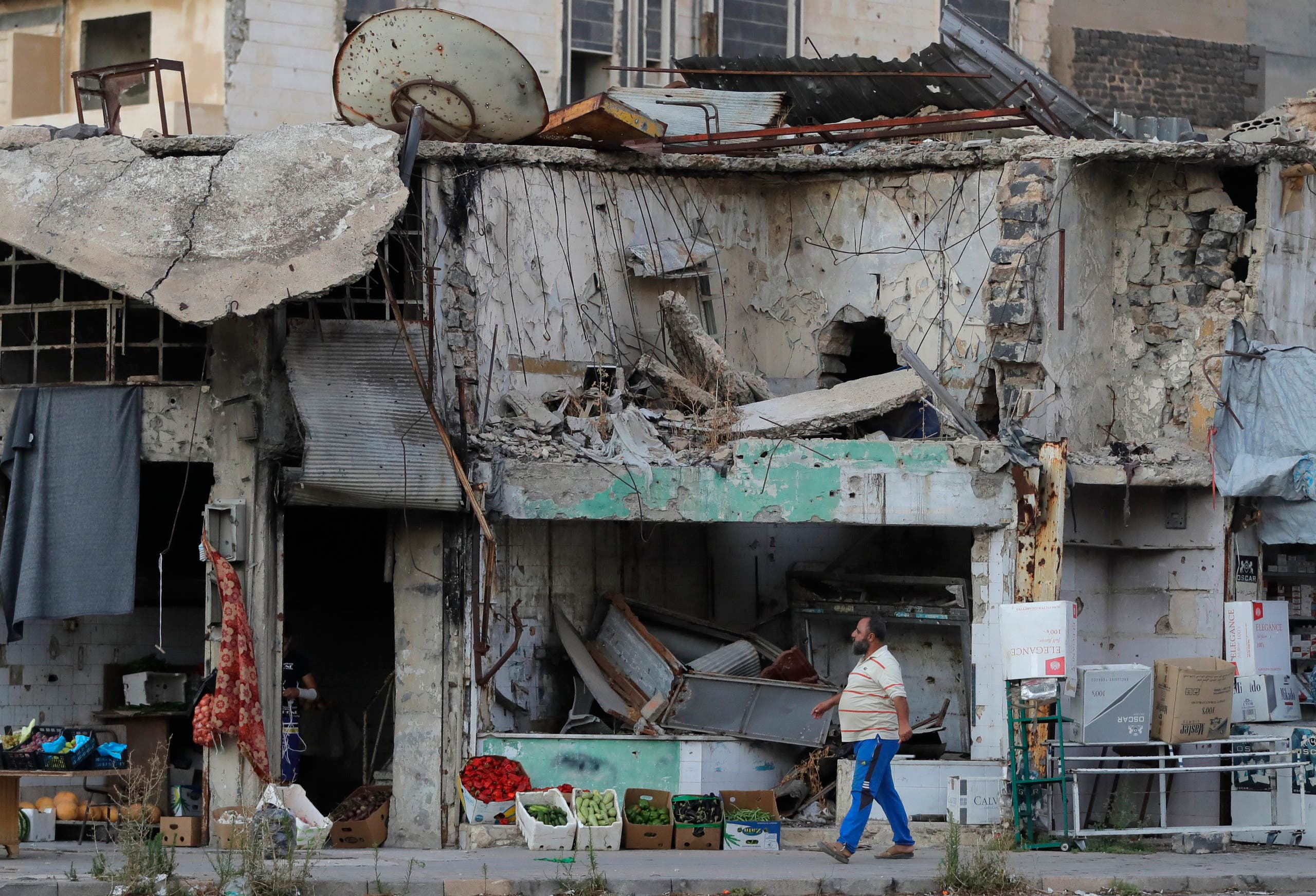 A man walks next to damaged buildings in the old town of Homs, Syria on Aug. 15, 2018. (AP)