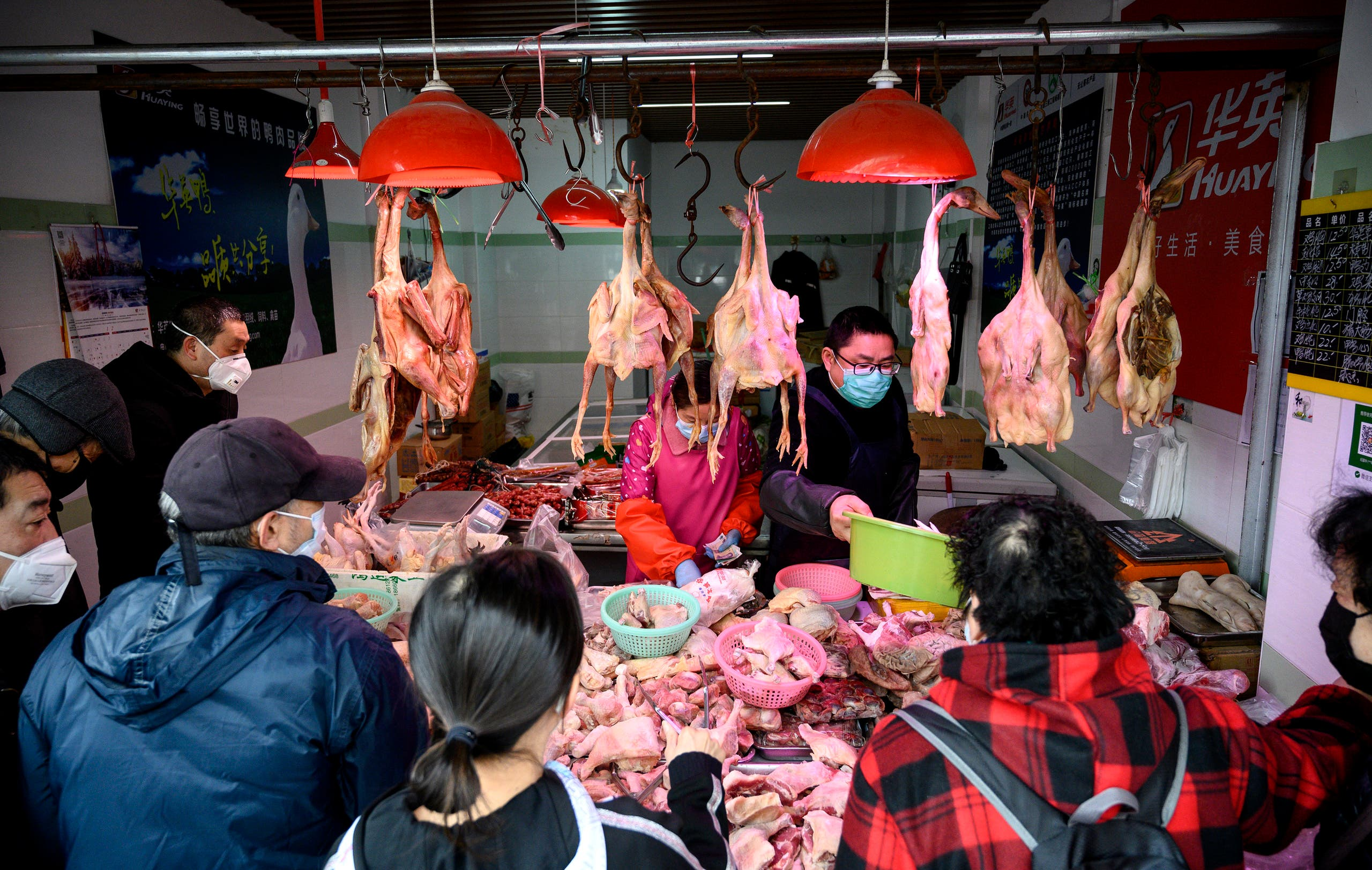 People wearing protective face masks shop at a chicken stall at a wet market in Shanghai on February 13, 2020.  (AFP)