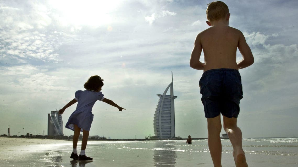 With the Burj Al Arab, seven star luxury hotel in the background, a girl points out a baby crab to other children as they play on the beach in in Dubai, United Arab Emirates, Thursday, Dec. 9, 2004. (AP)