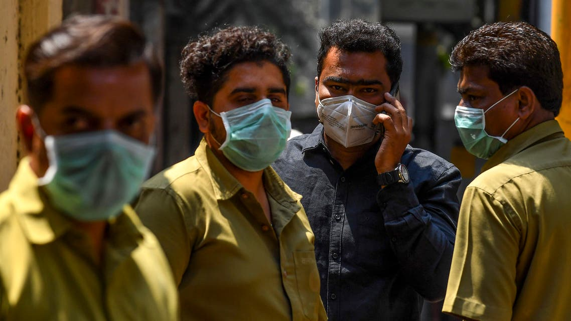 People wearing facemasks amid concerns over the spread of the COVID-19 novel coronavirus stand outside a hospital with a special ward for the virus in Mumbai on March 17, 2020. (AFP)