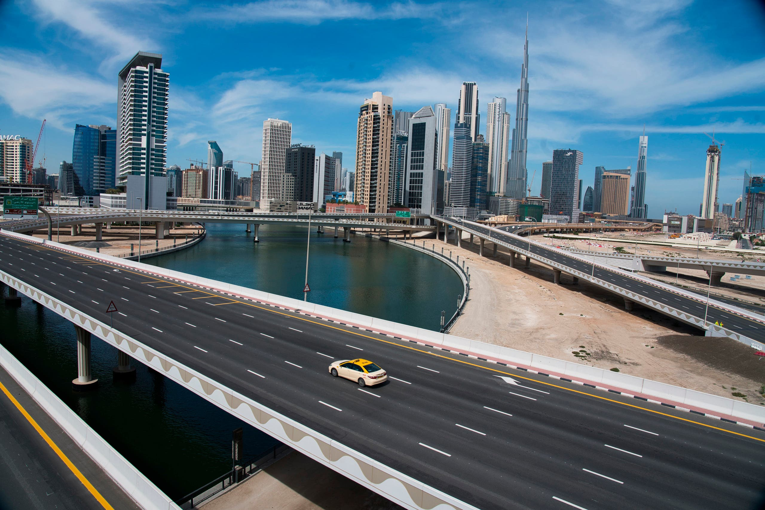 A lone taxi cab drives over a typically gridlocked highway with the Burj Khalifa, the world's tallest building, in the skyline behind it in Dubai, United Arab Emirates on April 6, 2020. (AP)