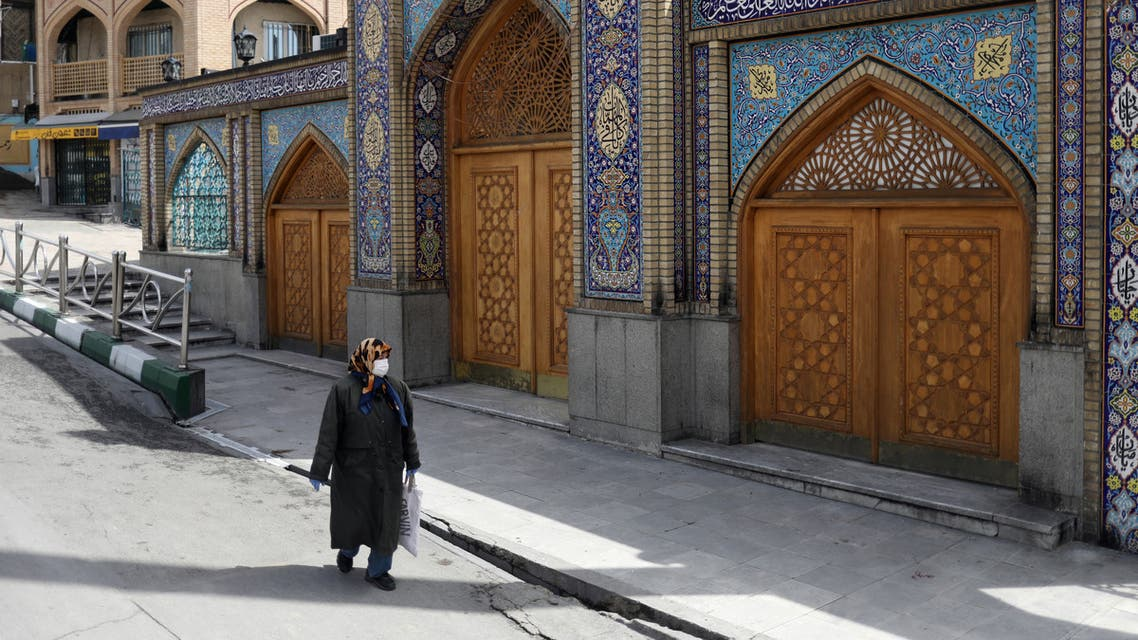 A woman wearing a protective face mask and gloves walks past the Imamzadeh Saleh shrine, amid fear of the coronavirus disease (COVID-19), in Tehran, Iran April 2, 2020. WANA (West Asia News Agency)/Ali Khara via REUTERS ATTENTION EDITORS - THIS PICTURE WAS PROVIDED BY A THIRD PARTY