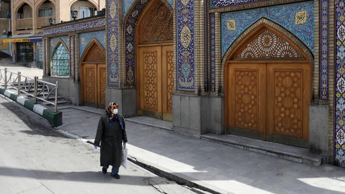 A woman wearing a protective face mask and gloves walks past the Imamzadeh Saleh shrine, amid fear of the coronavirus disease (COVID-19), in Tehran, Iran April 2, 2020. (WANA/Ali Khara via Reuters)
