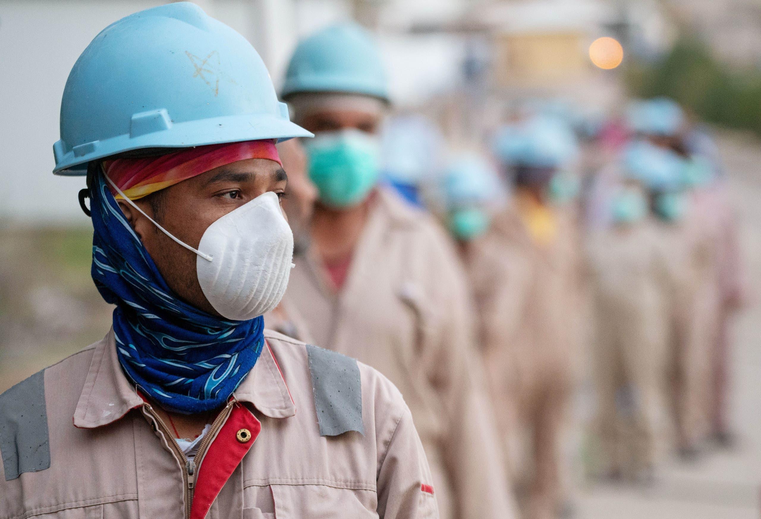 عمال يضعون كمامات واقية في موقع للانشاءات بالكويت
