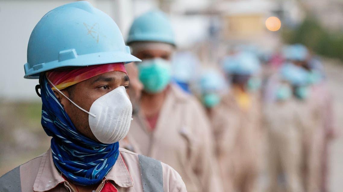 عمال يضعون كمامات واقية في موقع للانشاءات في الأحمدي الكويت - كورونا