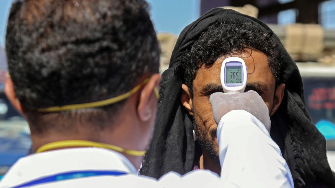 A health official checks the body temperature of man at the entrance of the city of Taez in southwestern Yemen on March 23, 2020 amid concerns over the spread of the COVID-19 novel coronavirus.