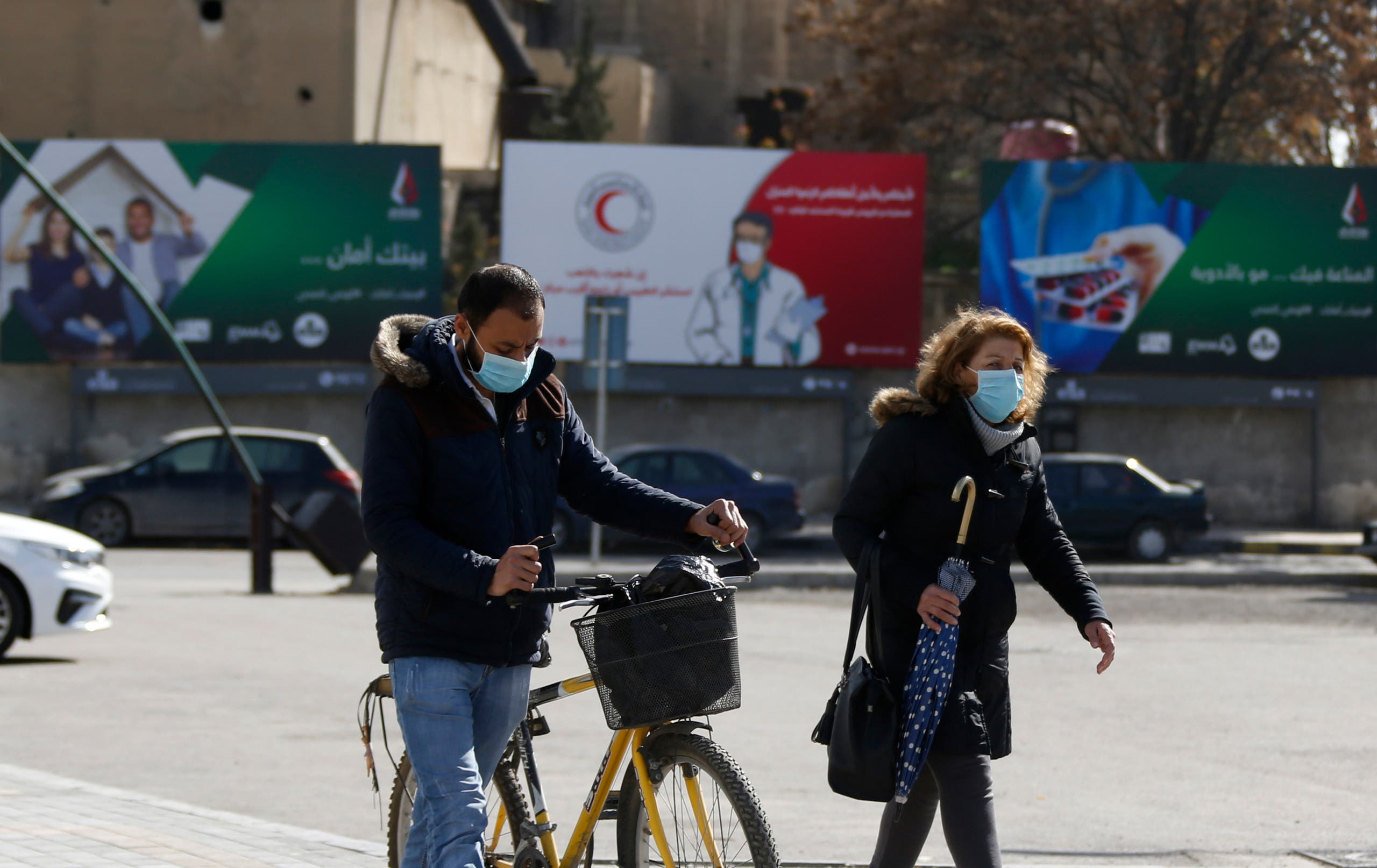 Syrians wearing face masks walk in front of posters informing about the novel coronavirus, in the capital Damascus on April 1, 2020. (AP)