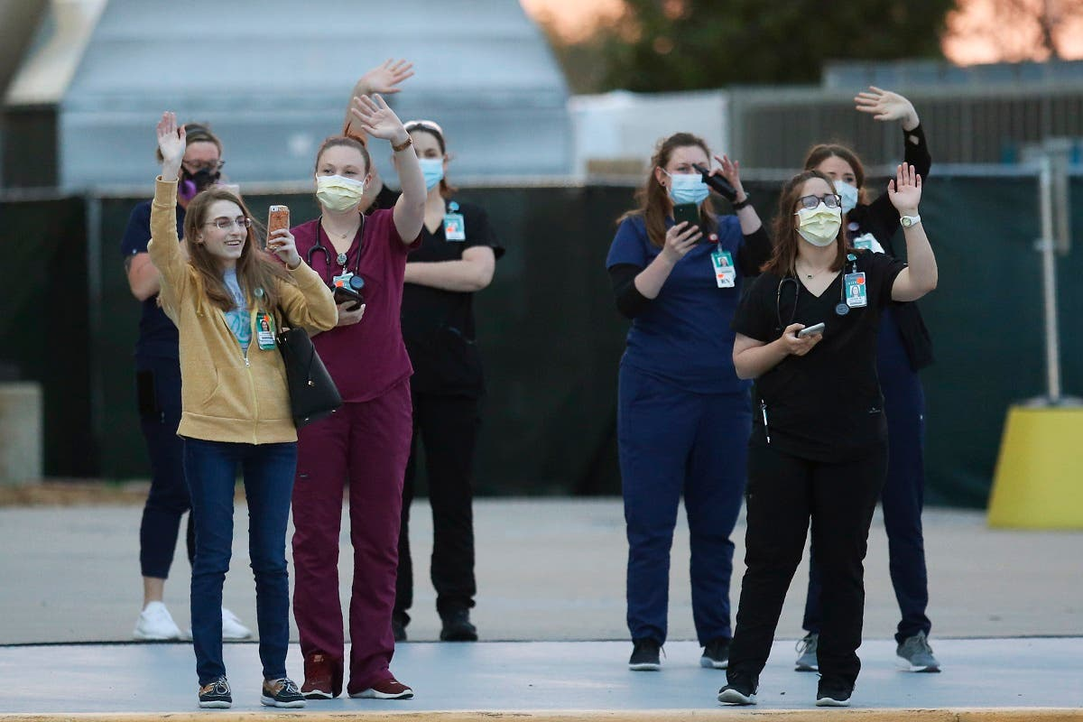 Hospital personnel wave and photograph people participating in a