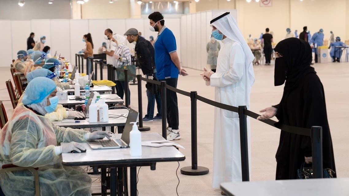 Kuwaitis, arriving from Europe, stand a safe distance apart to give their details to ministry of health officials in a makeshift coronavirus testing center. (File photo: Reuters)