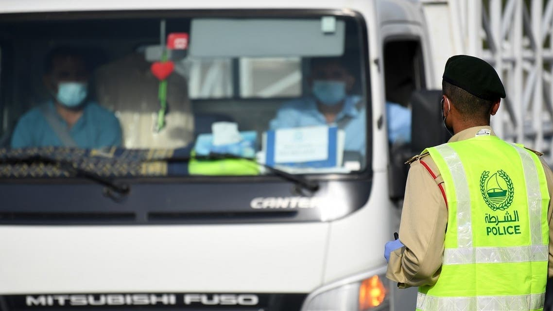 A policeman stops vehicles at a security checkpoint to examine passengers for exit permits, as people are only allowed essential travel due to a lockdown imposed by the UAE government as a measure during the COVID-19 coronavirus pandemic. (File photo: AFP)