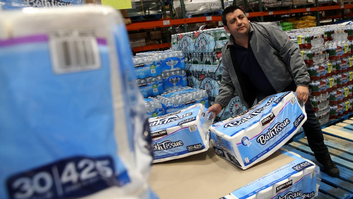 NOVATO, CALIFORNIA - MARCH 14: A customer picks up packages of toilet paper at a Costco store on March 14, 2020 in Novato, California. Some Americans are stocking up on food, toilet paper, water and other items after the World Health Organization (WHO) declared Coronavirus (COVID-19) a pandemic. Justin Sullivan/Getty Images/AFP